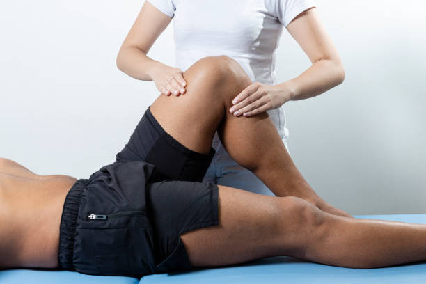 therapist treating injured knee of athlete male patient - sport physical therapy concept - physical therapy стоковые фото и изображения