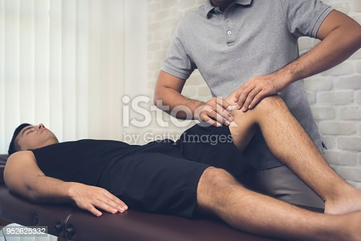 istock Therapist treating injured leg of athlete male patient in clinic 952625332
