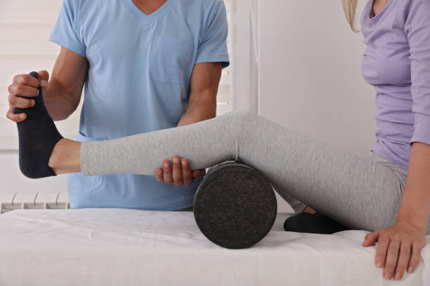 therapist treating knee of athlete female patient , physiotherapy, injury rehabilitation - medicina sportiva foto e immagini stock