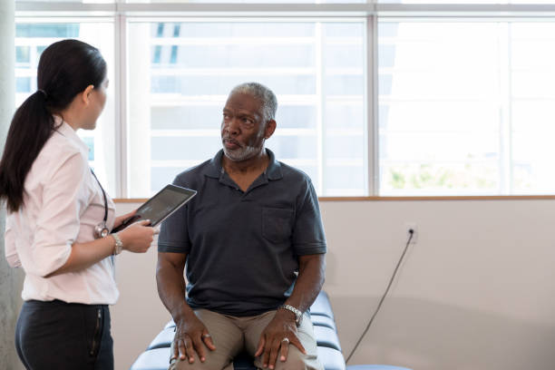Therapist uses digital tablet to diagnose mature patient's problem The mid adult female therapist uses her digital tablet to help diagnose the cause of the mature man's pain. outpatient stock pictures, royalty-free photos & images