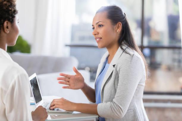 therapeut nutzt laptop während im gespräch mit patienten - gesundheitsfragen stock-fotos und bilder