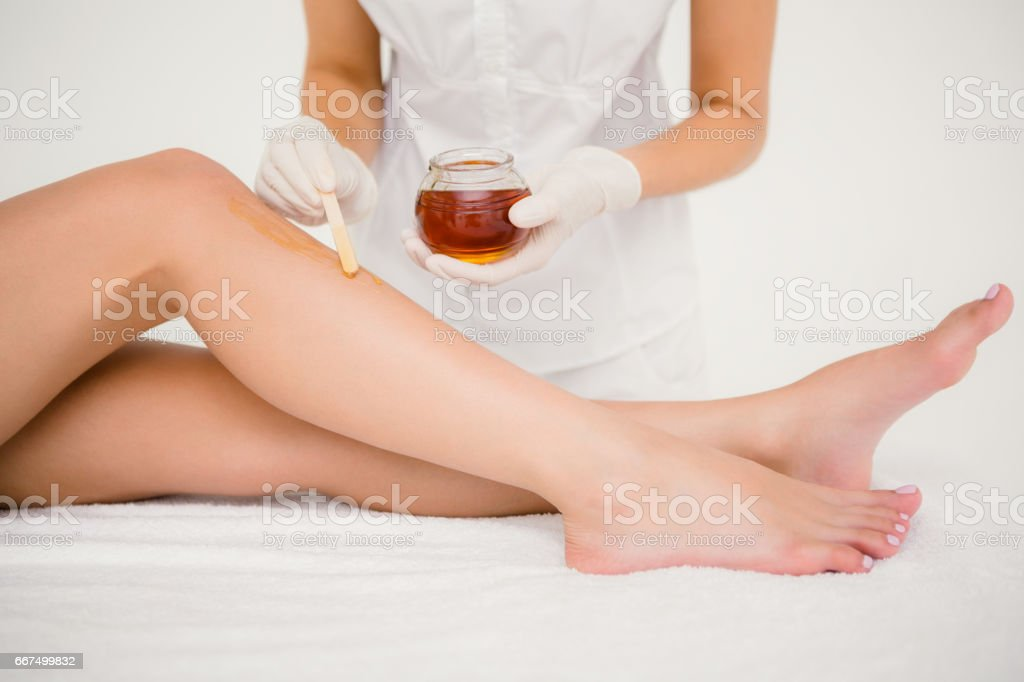 Therapist waxing womans leg at spa center foto stock royalty-free