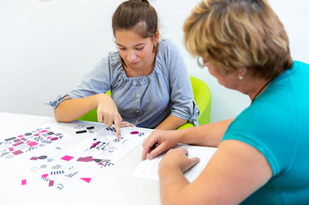 Therapist working with a teenage girl with learning difficulties to master logical tests. stock photo