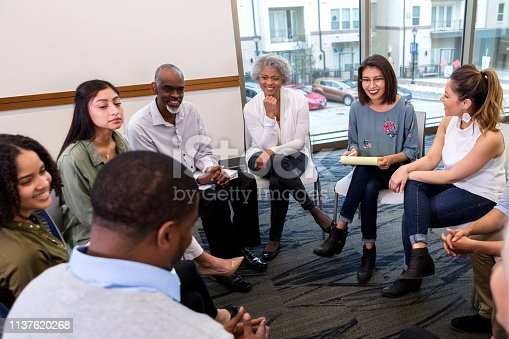 A group of people sit in a circle an laugh together during a group therapy session.