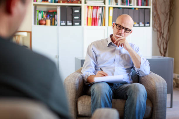 Therapy session, adult man talking to his psychotherapist stock photo