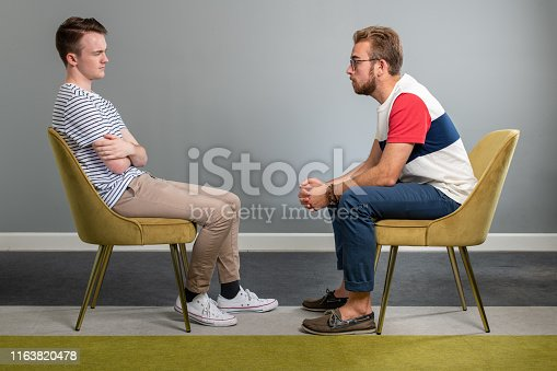 Two Men sit in identical chairs in an empty room while staring directly at each other. One Man leans over as the other sits back in his chair with his arms crossed.