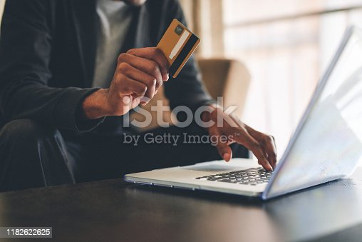 Cropped shot of an unrecognizable man using a credit card and a laptop to shop online at home