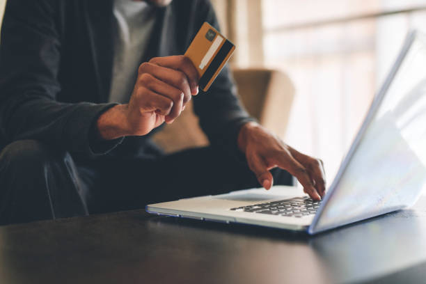 There are certain sales one cannot miss Cropped shot of an unrecognizable man using a credit card and a laptop to shop online at home home shopping stock pictures, royalty-free photos & images