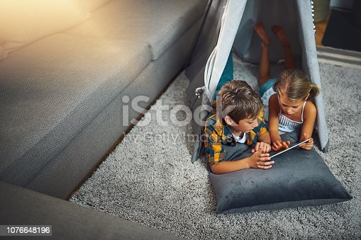 High angle shot of an adorable little boy and girl using a tablet together while chilling in a homemade tent in the living room at home