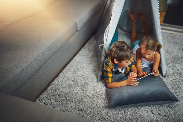 There are many educational apps for the kids these days High angle shot of an adorable little boy and girl using a tablet together while chilling in a homemade tent in the living room at home touchpad stock pictures, royalty-free photos & images