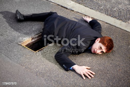 A young businessman lying on the ground with his leg stuck in a drain