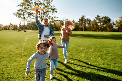 Portrait of cheerful parents with two kids running with kite in the park on a sunny day. Family, kids and nature concept. Horizontal shot.