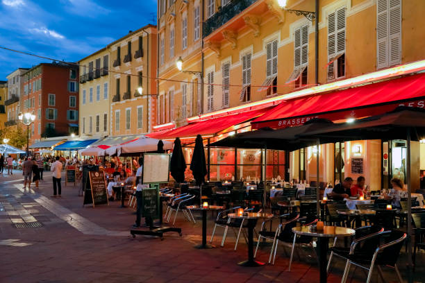 There are outdoor cafes near the buildings in the old town of Nice