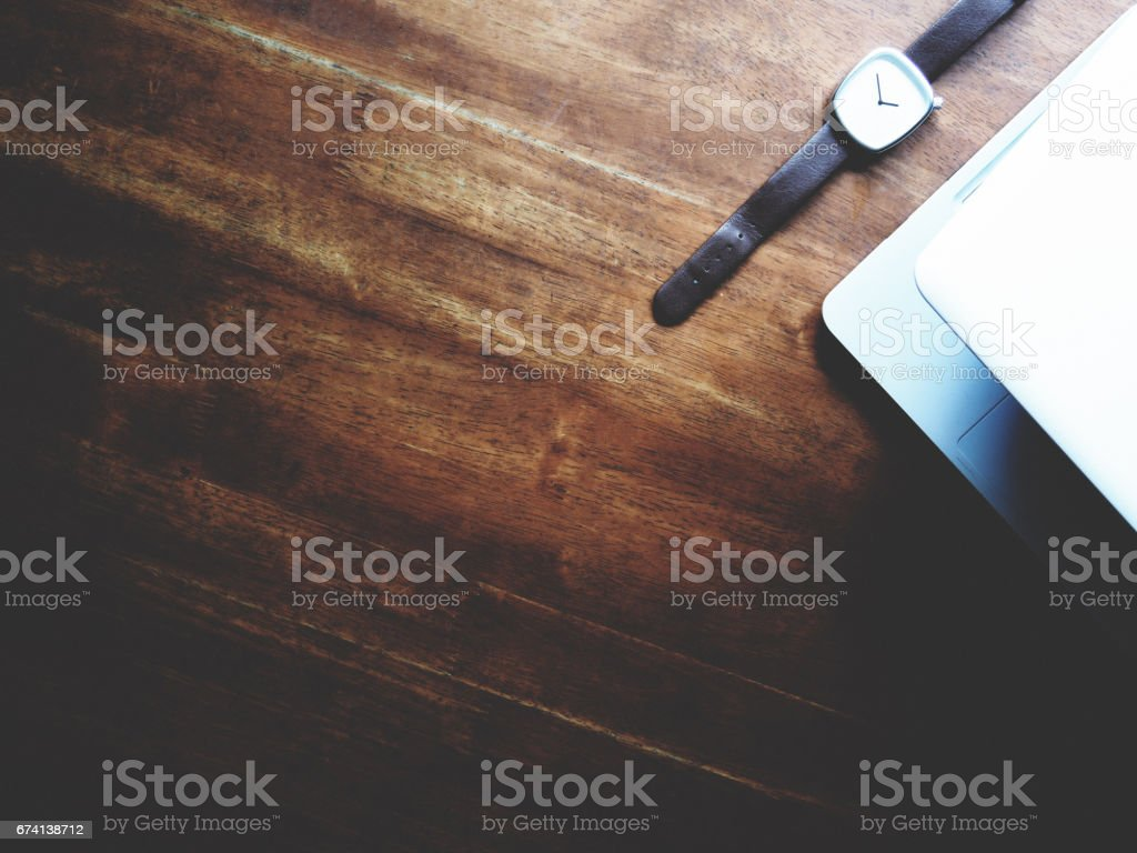 there are watch, laptop and leather bag on wooden table, minimal style, soft tone stock photo