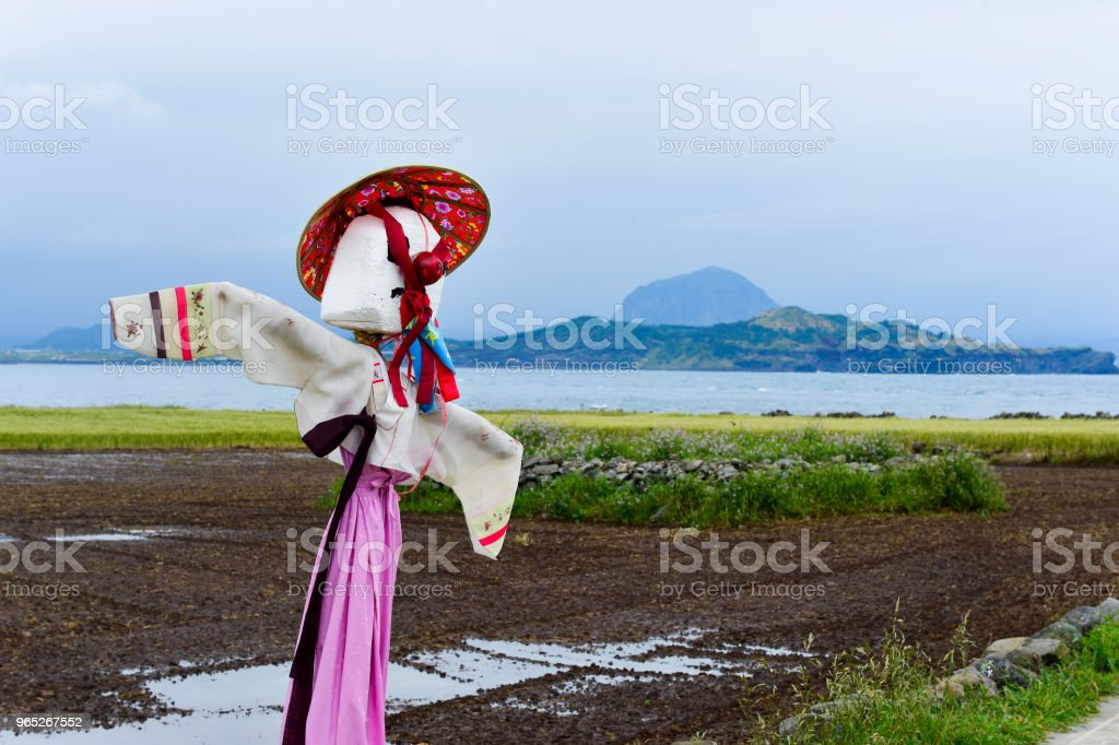 There is a scarecrow with Jejudo island and sea in the background. zbiór zdjęć royalty-free