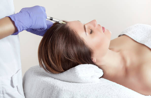 There is a woman and a cosmetologist, the woman is lying and the doctor is making the procedure of mesotherapy against hair loss and dandruff in a beauty salon.Strengthen hair and their growth. stock photo