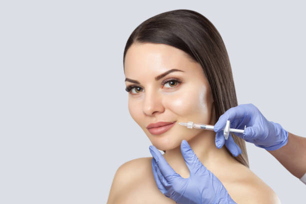 There is a woman, who is making the Lips augmentation procedure  in a beauty salon.Cosmetology skin care. stock photo