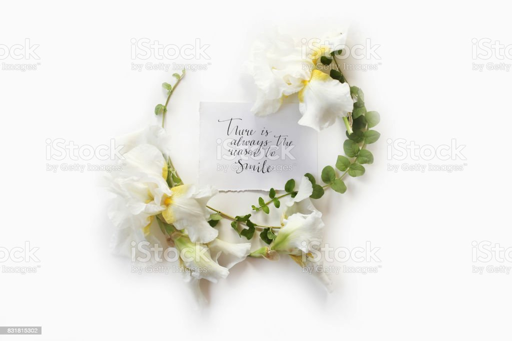 There is always the reason to smile in calligraphy style on paper in middle of wreath made of fresh Iris white flowers and green branches on white background. Flat lay, top view.