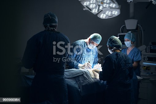 Shot of a team of surgeons performing a surgery in an operating theatre