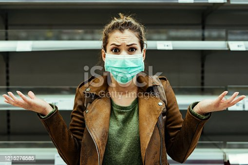 Shocked woman with protective mask gesturing while standing in front of empty shelf at supermarket during coronavirus pandemic.