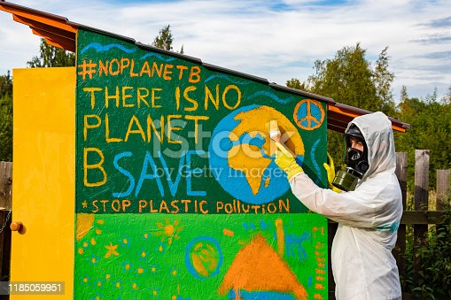 A man in a gas mask and a chemical protection suit paints the concept of the environment. There is no planet B. Save the planet earth. Stop plastic pollution.