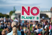 rear view woman at climate change protest fridays for future holding no planet b sign in front of big crowd at demonstration, shallow focus, background blurred