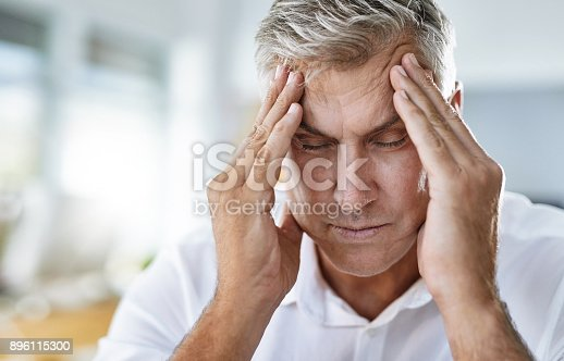 Shot of a mature businessman suffering with a headache at work