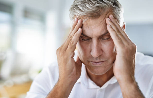 There is no way I can work with this headache Shot of a mature businessman suffering with a headache at work headache stock pictures, royalty-free photos & images