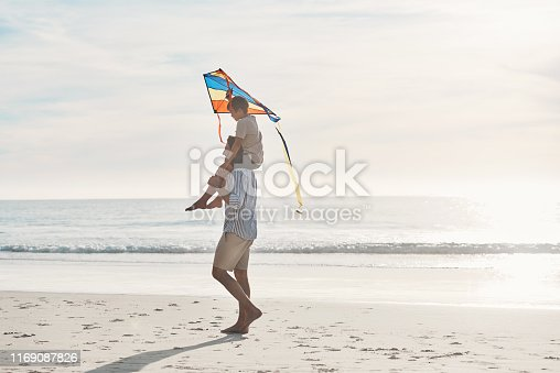 Full length shot of a young boy being carried on his father's shoulders and holding a kite on the beach