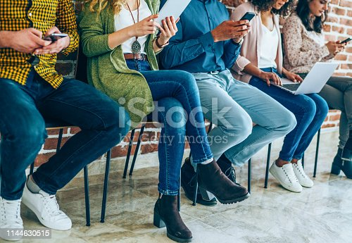 Group of young people with smart phones, digital tablets and laptop sitting in a row in chairs