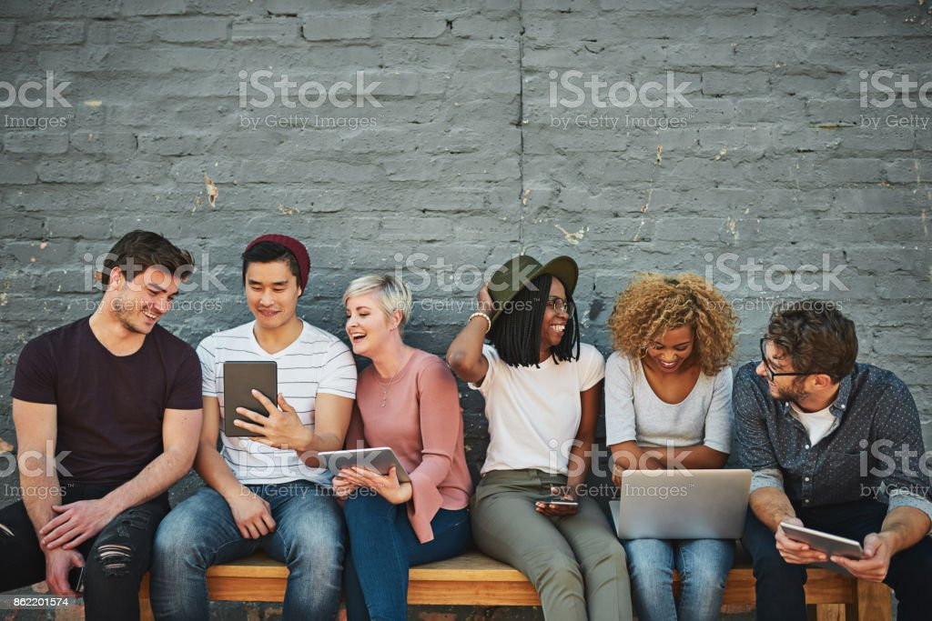 There is so much fun to have with social networking Shot of a diverse group of people social networking outside Adult Stock Photo