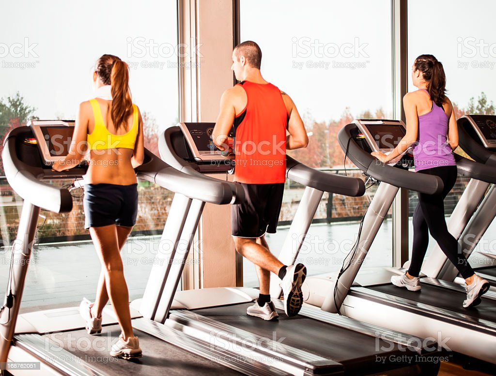 There people running on treadmills in a gym stock photo