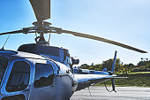 Shot of an helicopter outside at an air port during the day waiting to be taken up into the air