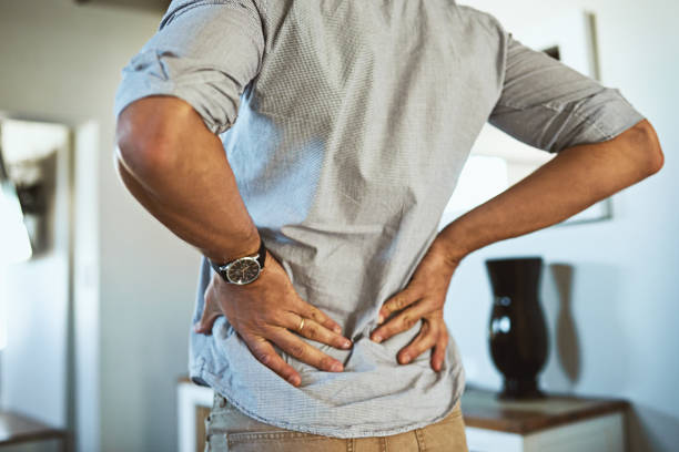 There's a bit of pain at my lower back Rearview shot of an unrecognizable man holding his back in discomfort due to pain inside at home back pain stock pictures, royalty-free photos & images