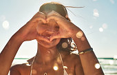 Portrait of a beautiful young woman making a heart shaped gesture with her hands at the beach