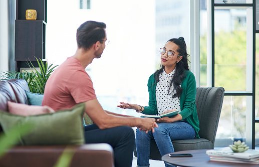 Shot of a young man and woman having a discussion in a modern office
