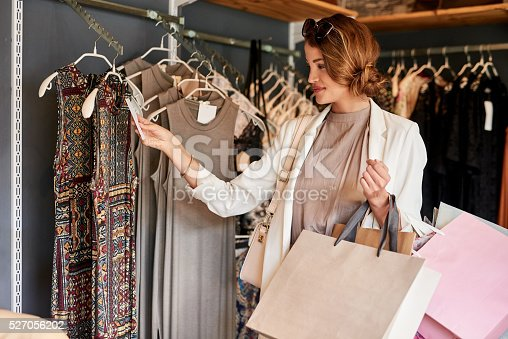 Shot of a young woman looking at a few items in a boutique