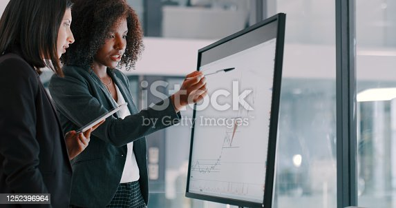 Shot of two young businesswomen using an interactive whiteboard to analyse data in a modern office