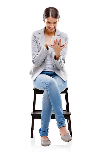 There's always something new on the net Studio shot of a beautiful young woman sitting on a stool and using a digital tablet against a white backgroundhttp://195.154.178.81/DATA/i_collage/pu/shoots/785081.jpg skinny jeans stock pictures, royalty-free photos & images