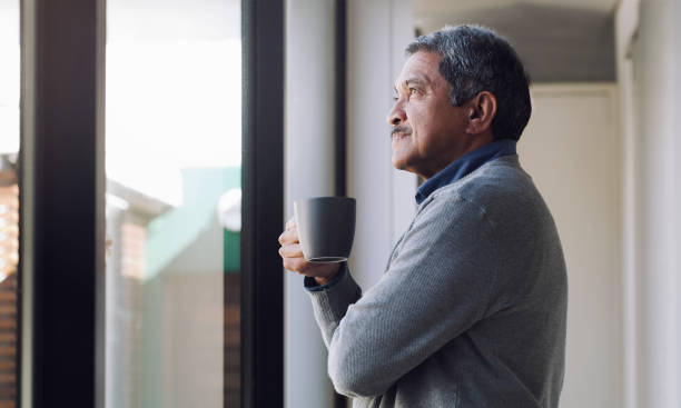 There's always something to look forward to Shot of a senior man drinking coffee and looking thoughtfully out of a window 65 69 years stock pictures, royalty-free photos & images