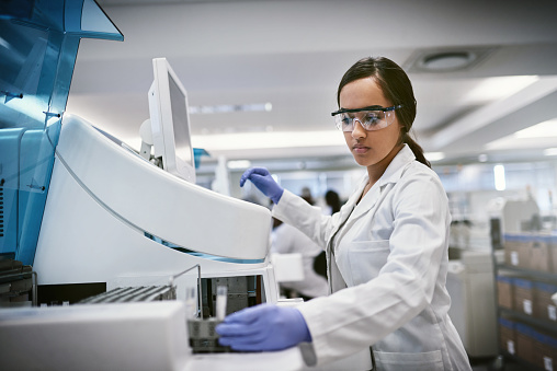 Shot of a young woman using a machine to conduct a medical test in a laboratory