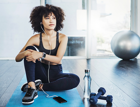 Shot of a sporty young woman listening to music while exercising in a studio