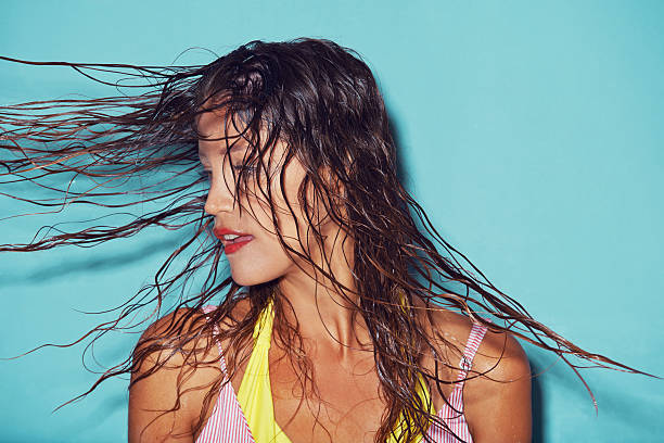 There's just something about wet hair... Shot of a young woman flipping her wet hair against a blue background wet hair stock pictures, royalty-free photos & images