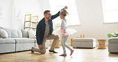 Shot of a father dancing with his little daughter at home
