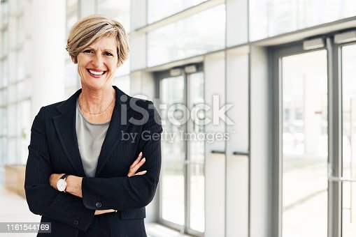 Cropped portrait of a confident mature businesswoman standing with her arms folded in a modern office