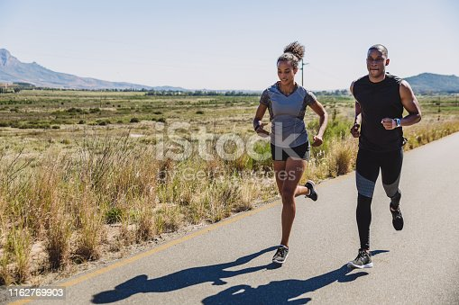 Shot of two sporty young people running out on a country road
