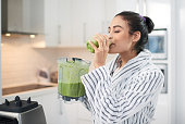 Cropped shot of a woman drinking a smoothie at home