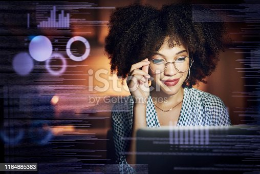 Shot of a young female programmer using a laptop while working late in her office