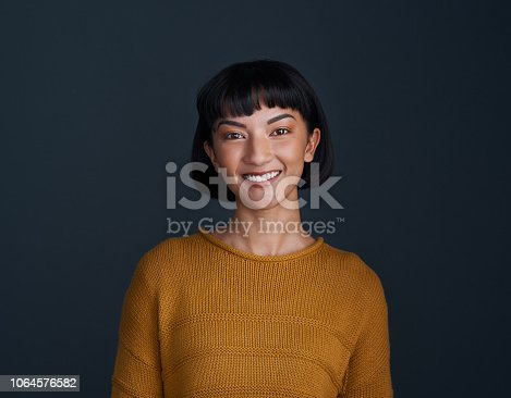 Studio shot of an attractive young woman posing against a dark background