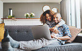 Shot of a young woman hugging her husband while he uses a laptop on the sofa at home